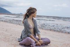 Bella giovane donna alla moda che si siede sulla sabbia sulla spiaggia Immagini Stock