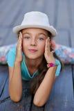 Bella giovane donna alla moda che si siede sulle spaccature sul backg Fotografia Stock