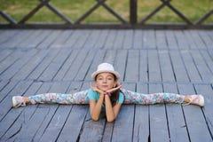 Bella giovane donna alla moda che si siede sulle spaccature sul backg Immagini Stock Libere da Diritti