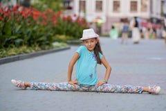 Bella giovane donna alla moda che si siede sulle spaccature sul backg Fotografia Stock Libera da Diritti