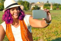 Bella giovane donna alla moda dei pantaloni a vita bassa con capelli ricci rosa che gode del giorno, prendente selfie fotografia stock libera da diritti