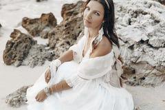 Bella giovane donna alla moda di boho che si siede sulla spiaggia al sunse Fotografia Stock