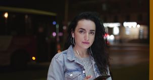 Bella giovane donna alla moda felice alla moda in Jean Jacket con le cuffie bianche e lungamente i capelli ricci scuri occupati c archivi video