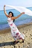 Bella giovane donna alla spiaggia con la sciarpa bianca Fotografia Stock