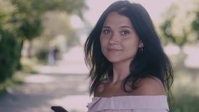 Bella giovane donna alla via della città e tornitura alla macchina fotografica ed a sorridere Movimento lento archivi video