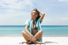 Bella giovane donna allegra in bikini che si siede sulla spiaggia Fotografie Stock