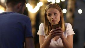 Bella giovane donna annoiata alla cattiva data facendo uso del suo telefono video d archivio