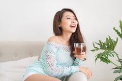 Bella giovane donna asiatica che beve il suo tè di mattina sopra un brea Fotografia Stock Libera da Diritti