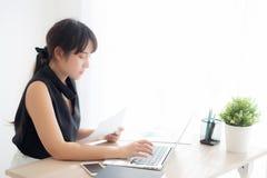 Bella giovane donna asiatica che lavora e che scrive con il computer portatile all'ufficio, donna di affari che guarda analisi de fotografia stock