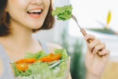 Bella giovane donna asiatica che mangia l'insalata della verdura fresca Loosin Immagini Stock