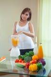 Bella giovane donna asiatica che produce il frullato della frutta Immagine Stock