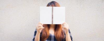 Bella giovane donna asiatica che si nasconde dietro una derisione in bianco sul libro sul fondo del muro di cemento Immagini Stock