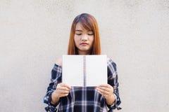Bella giovane donna asiatica che si nasconde dietro una derisione in bianco sul libro sul fondo del muro di cemento immagini d'an Immagine Stock Libera da Diritti