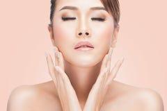 Bella giovane donna asiatica con gli occhi chiusi che toccano il suo fronte Fotografia Stock Libera da Diritti