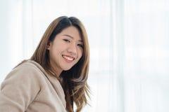 Bella giovane donna asiatica felice che sveglia nella mattina, sedendosi sul letto, allungando nella camera da letto accogliente, Fotografia Stock