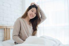 Bella giovane donna asiatica felice che sveglia nella mattina, sedendosi sul letto, allungando nella camera da letto accogliente, Fotografie Stock