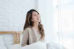 Bella giovane donna asiatica felice che sveglia nella mattina, sedendosi sul letto, allungante nella camera da letto accogliente Immagine Stock Libera da Diritti