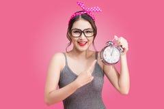 Bella giovane donna asiatica sorridente che mostra sveglia sul rosa Fotografia Stock Libera da Diritti