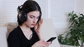 Bella giovane donna attraente che si siede sul sofà e che ascolta la musica fotografia stock
