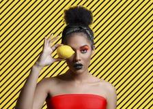Bella giovane donna attraente con trucco creativo e limone vicino all'occhio fotografia stock