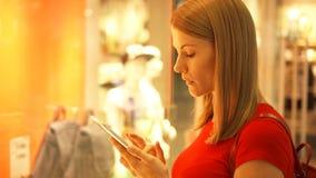 Bella giovane donna attraente vicino al negozio di finestra in centro commerciale Controllo dei prezzi del deposito sul suo smart stock footage
