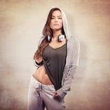 Bella giovane donna in attrezzatura urbana con le cuffie Colpo dello studio Immagini Stock Libere da Diritti