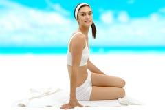 Bella giovane donna in biancheria intima bianca che si siede sull'asciugamano Fotografia Stock Libera da Diritti