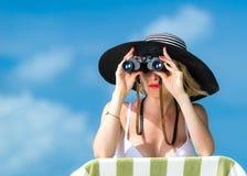 Bella giovane donna in bikini che esamina tramite il binocolo la spiaggia tropicale Immagini Stock