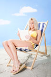 Bella giovane donna in bikini che legge un libro Fotografia Stock