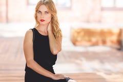 Bella giovane donna bionda alla moda che si siede sul banco all'aperto Fotografia Stock
