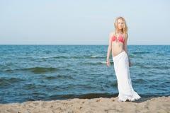 Bella giovane donna bionda che cammina su una spiaggia immagini stock