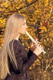 Bella giovane donna bionda che gioca il registratore della flauto nella foresta di autunno Fotografia Stock