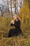 Bella giovane donna bionda che gioca il registratore della flauto nella foresta di autunno Immagine Stock Libera da Diritti