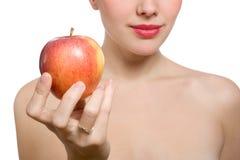 Bella giovane donna bionda che offre mela rossa fotografia stock libera da diritti
