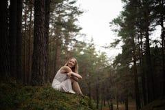 Bella giovane donna bionda che si siede nella crisalide della foresta in vestito bianco in legno sempreverde immagini stock libere da diritti