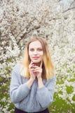 Bella giovane donna bionda che sta davanti alla fioritura meravigliosa Immagine Stock Libera da Diritti