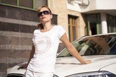 Bella giovane donna bionda con gli occhiali da sole circa l'automobile fotografia stock