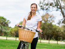 Bella giovane donna bionda con la bici in parco Immagini Stock