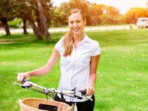 Bella giovane donna bionda con la bici in parco Fotografie Stock