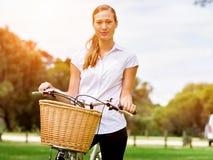 Bella giovane donna bionda con la bici in parco Fotografia Stock Libera da Diritti