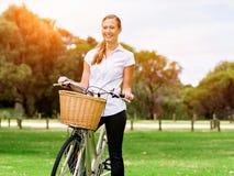 Bella giovane donna bionda con la bici in parco Immagine Stock Libera da Diritti