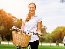 Bella giovane donna bionda con la bici in parco Fotografia Stock