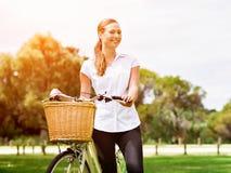Bella giovane donna bionda con la bici in parco Immagine Stock