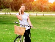Bella giovane donna bionda con la bici in parco Fotografie Stock Libere da Diritti