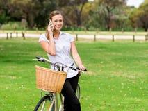 Bella giovane donna bionda con la bici in parco che discute a fondo telefono Fotografia Stock