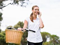 Bella giovane donna bionda con la bici in parco che discute a fondo telefono Immagine Stock