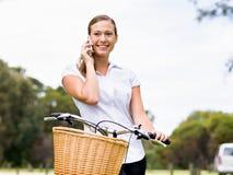 Bella giovane donna bionda con la bici in parco che discute a fondo telefono Fotografie Stock