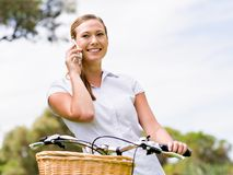 Bella giovane donna bionda con la bici in parco che discute a fondo telefono Fotografia Stock Libera da Diritti