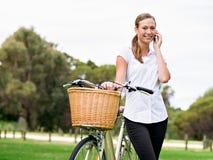 Bella giovane donna bionda con la bici in parco che discute a fondo telefono Immagini Stock