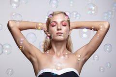 Bella giovane donna bionda con le bolle di sapone su backgroun grigio immagini stock libere da diritti